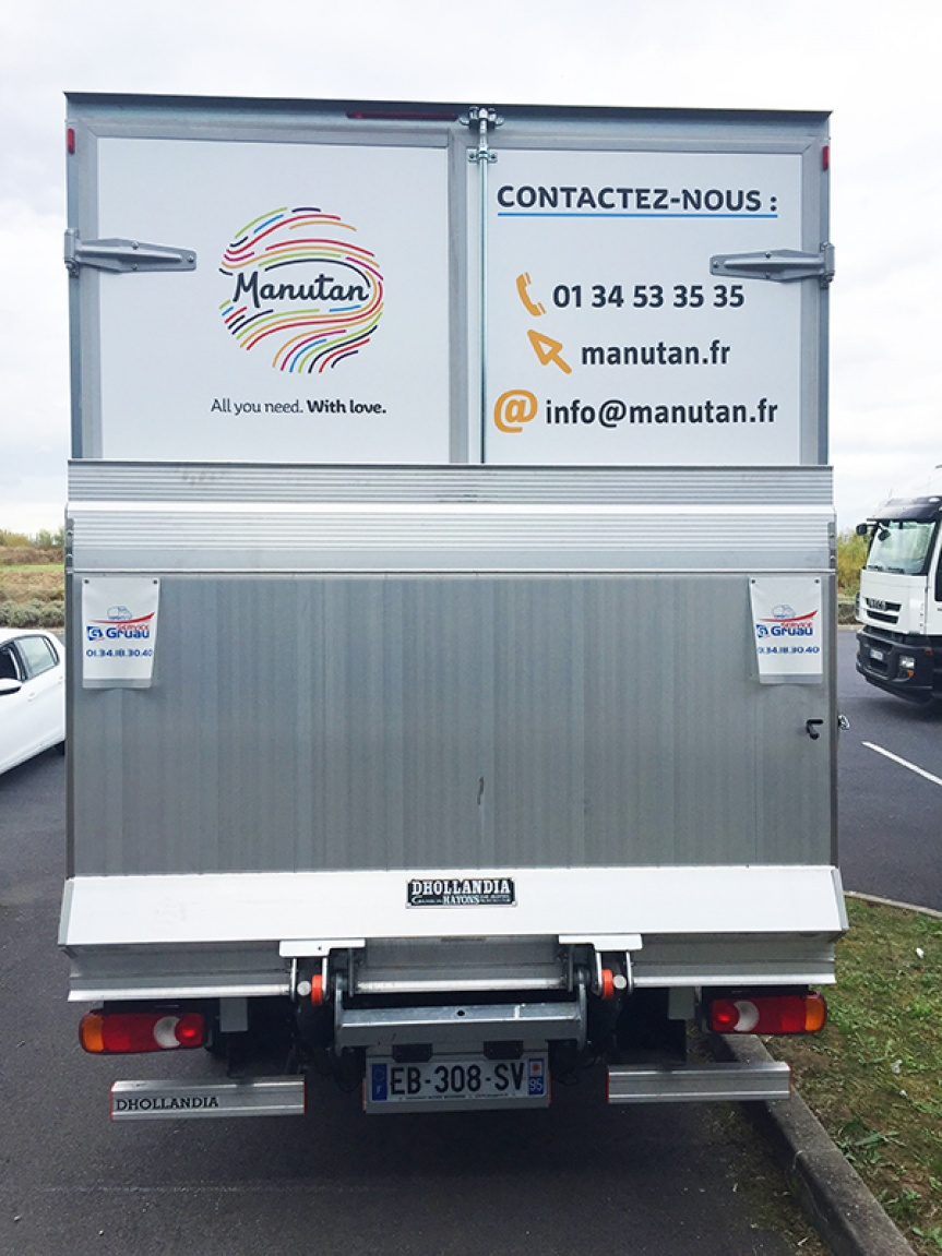 Photograph of a transport truck seen from behind with Manutan contact details displayed.