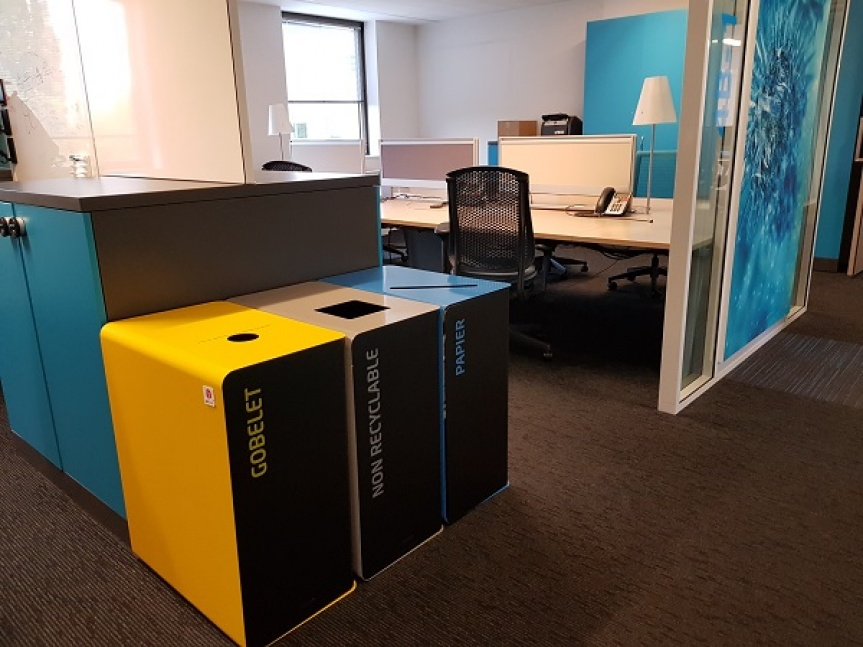 Photograph of three metal trash cans for corporate waste management.